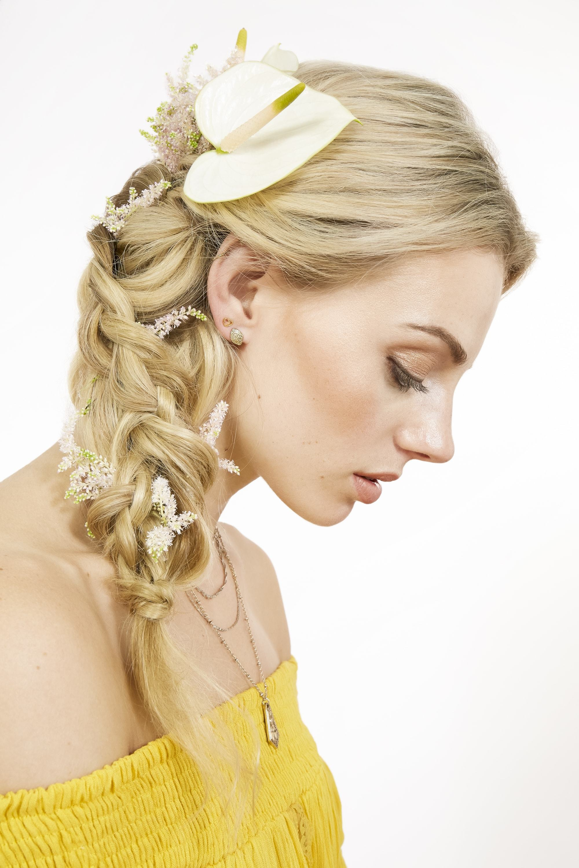 Braids for long hair: Model with blonde hair in side braid with flowers wearing a yellow summer top.