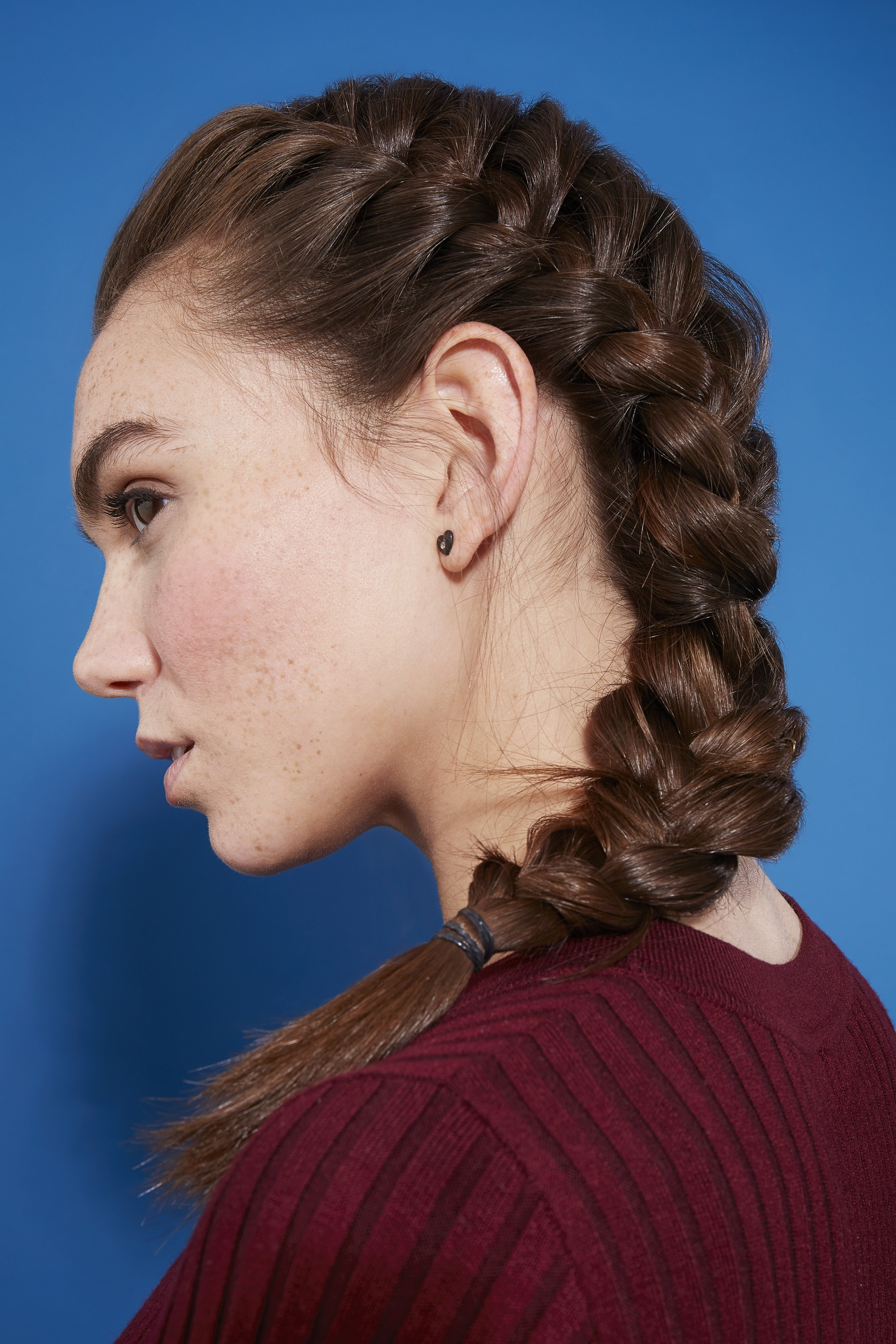 Braids for long hair: Woman with dark brown hair in side French braid against a blue backdrop.