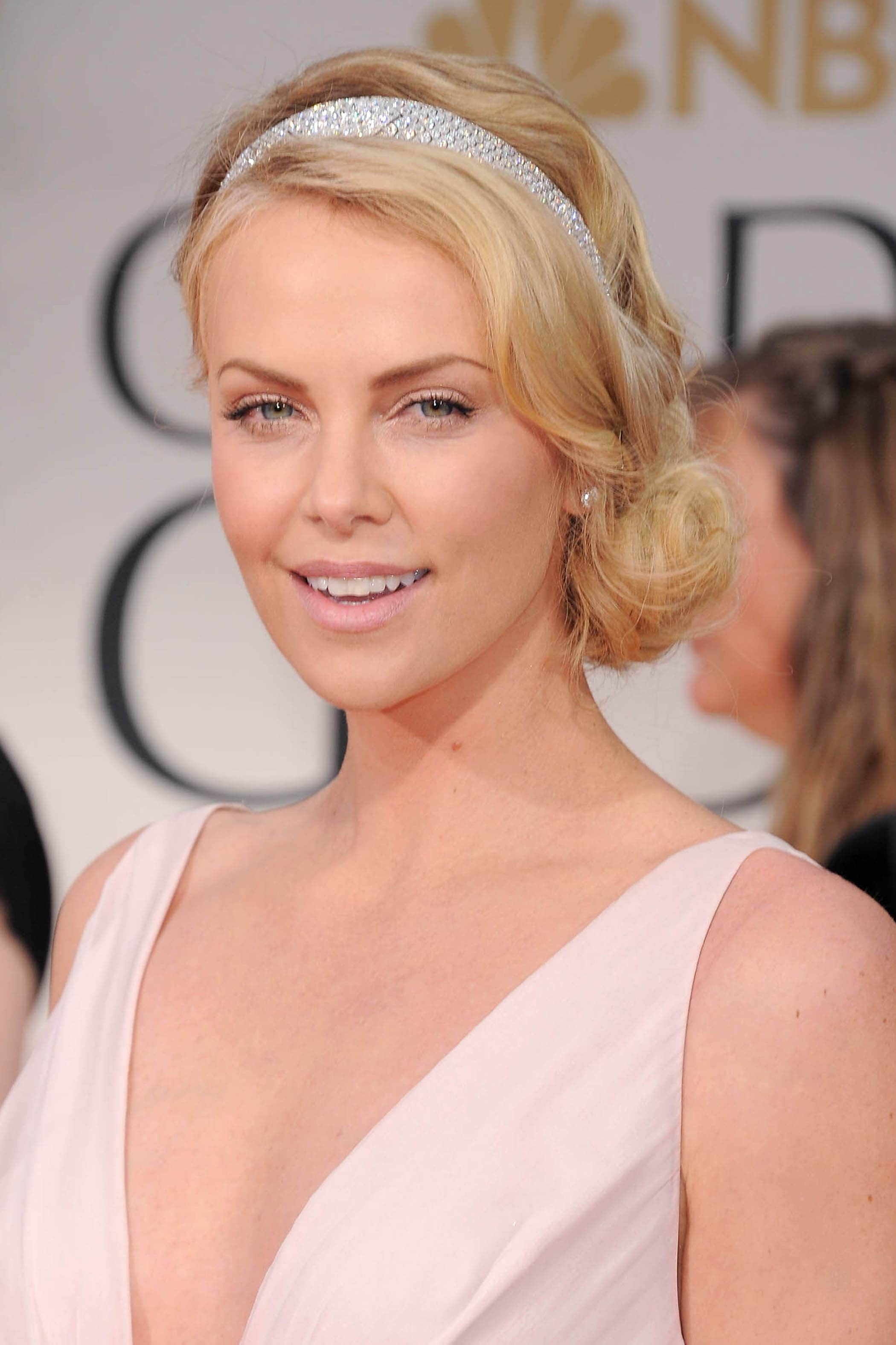 actress charlize theron with a blonde wavy side chignon hairstyle