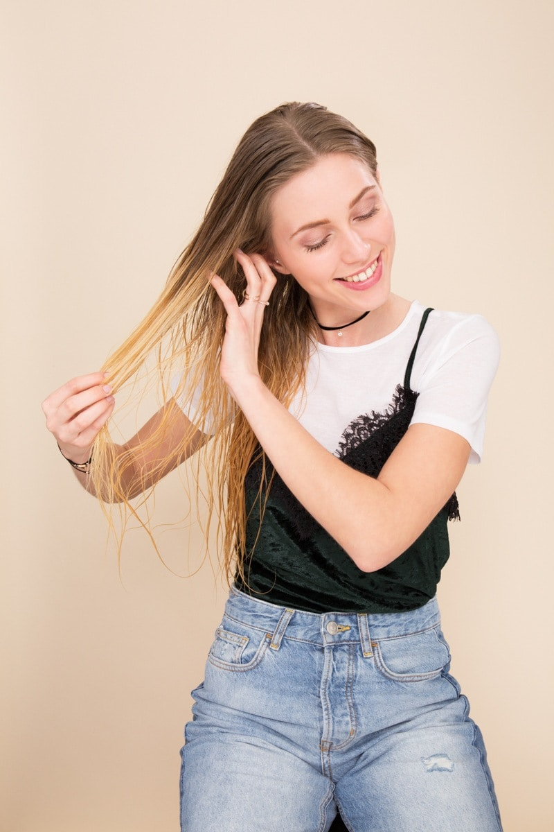 Deep conditioner: Blonde woman wearing a white tshirt with a black lace cami top and jeans running her hands through her wet hair