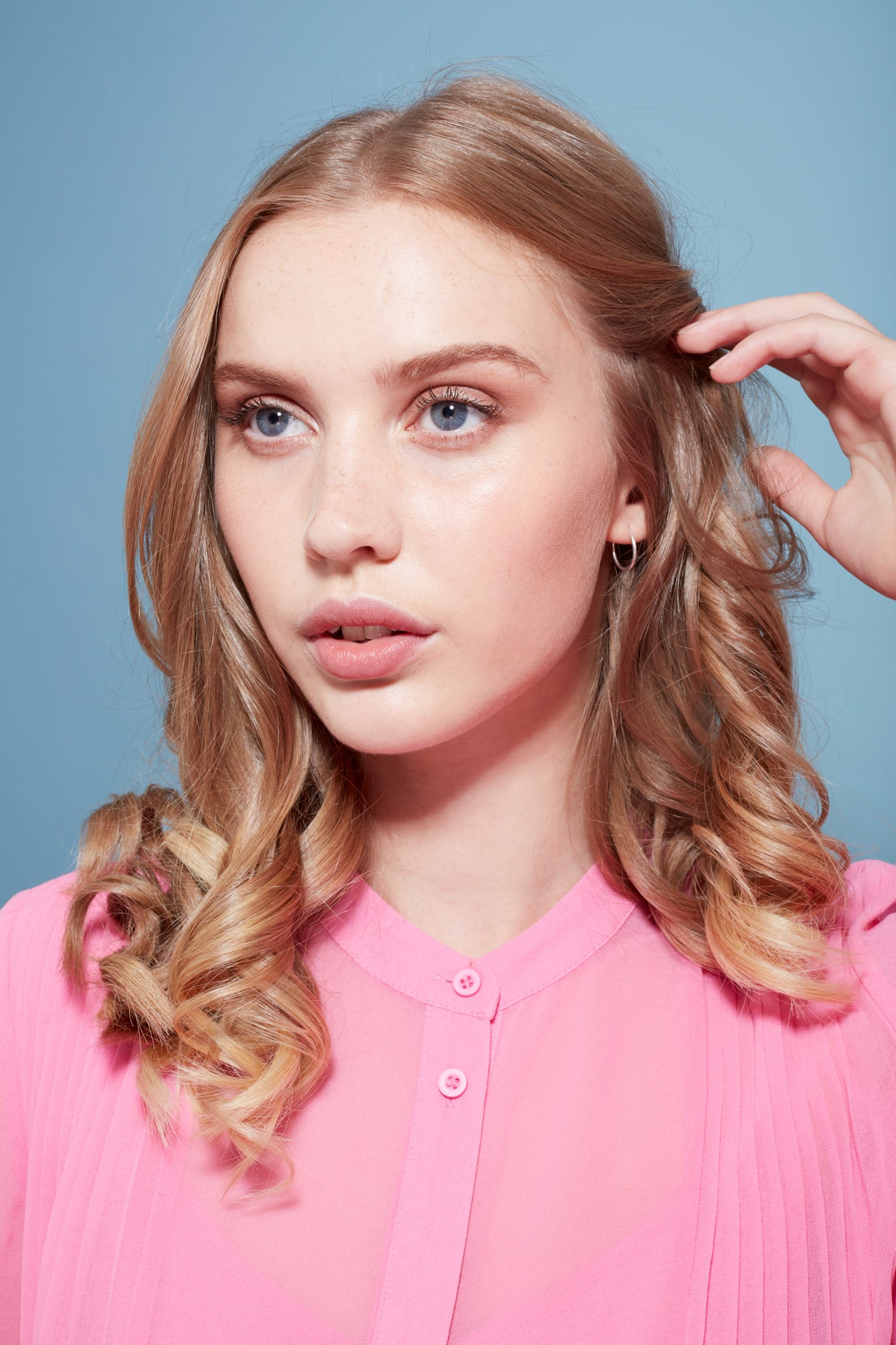 Keratin shampoo: Blonde model touching her medium length curly hair wearing a pink blouse.