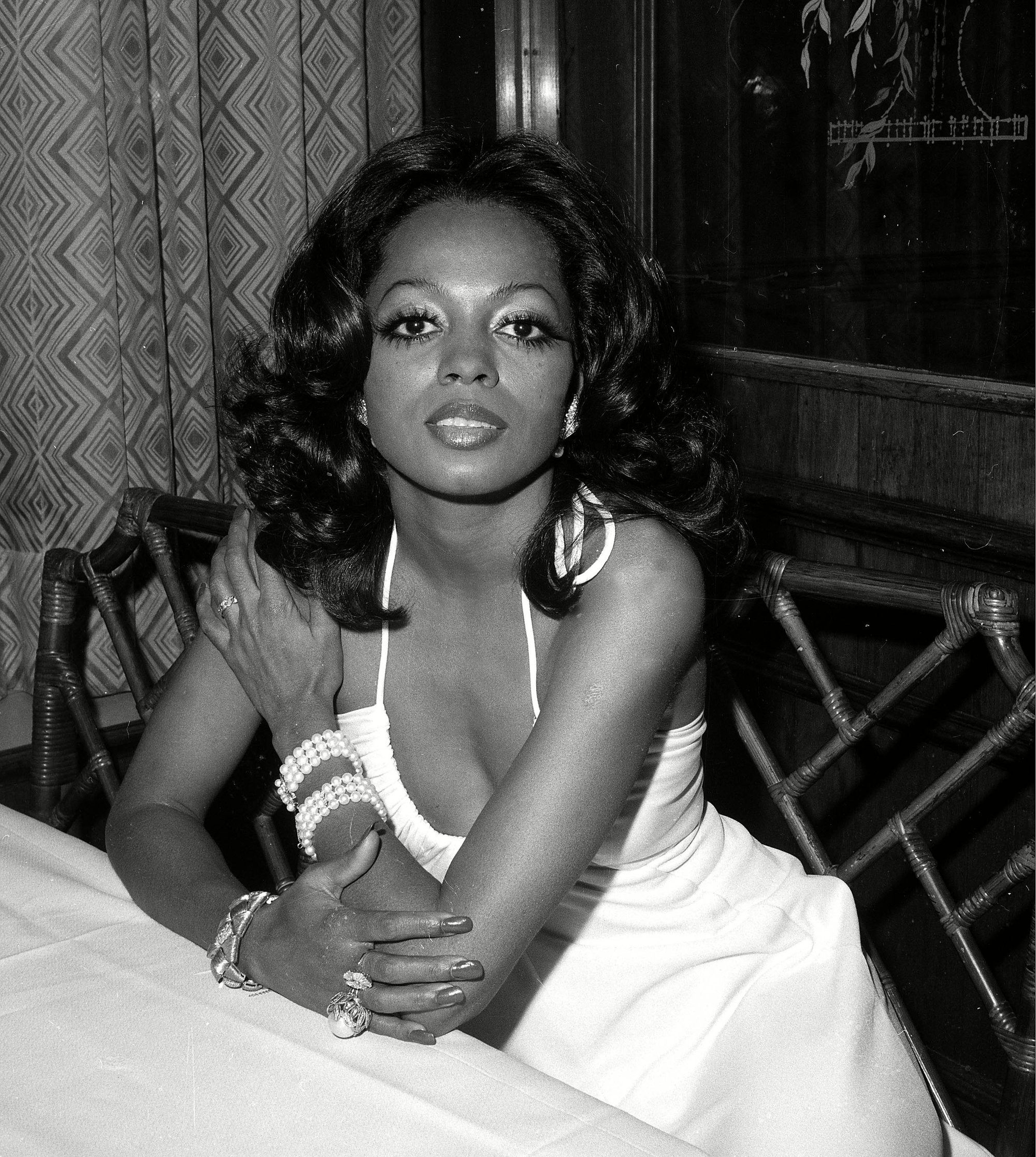 70s hairstyles: Diana Ross black and white image with her dark brown medium shoulder length hair styled with loose waves sitting at a table