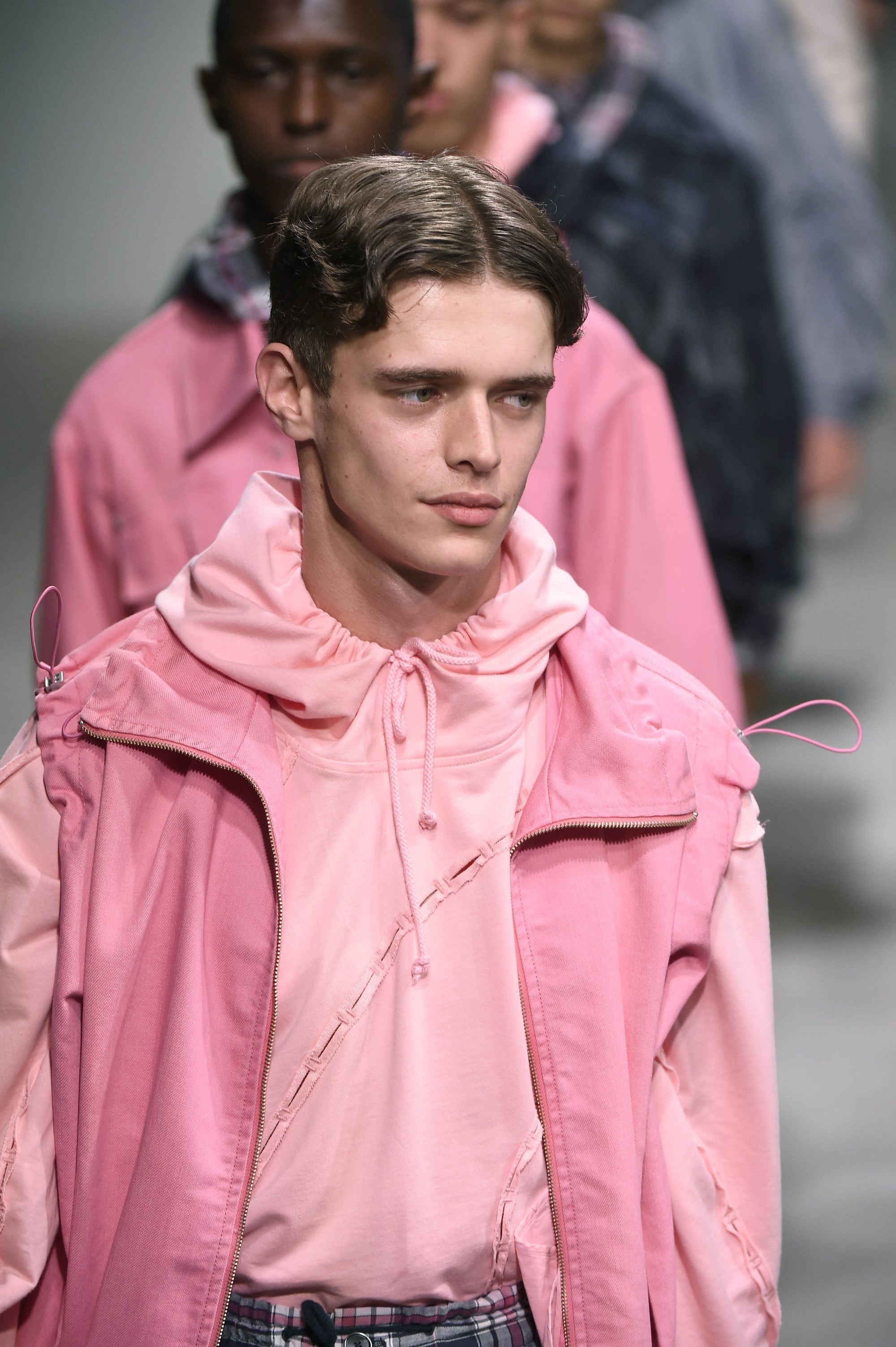 male model with curly curtains hair style, wearing pink on the Feng Chen Wang show