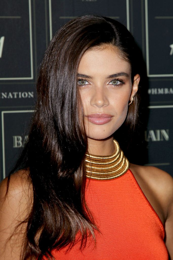 sarah sampaio on the balmain red carpet with dark brown hair styled to the side wearing red