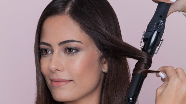 model using a curling wand on her brown hair