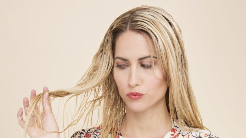 Deep conditioner: Blonde model wearing a floral wrap blouse and striped trousers with wet hair