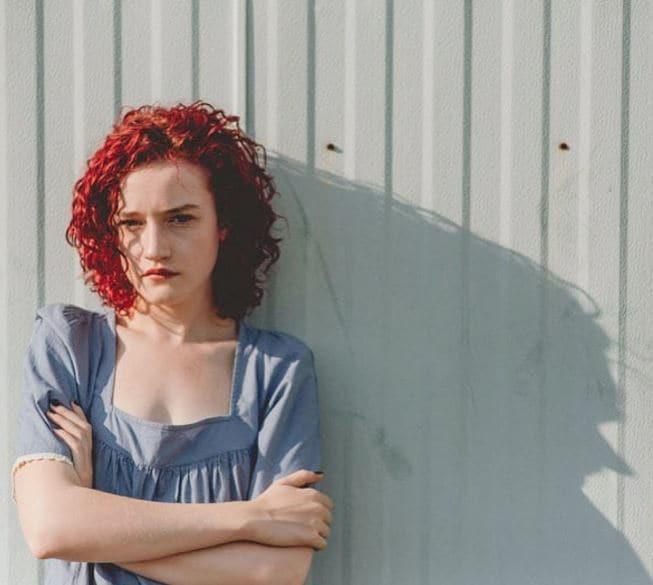 Julia Garner shoulder length vibrant red corkscrew curly hair