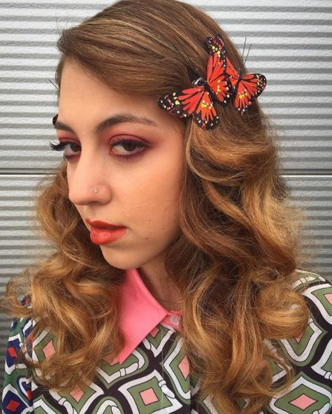 girl with golden brown hair with vontage waves and red butterfly clips