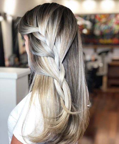 The back view of a blonde woman with a very loose side French plait