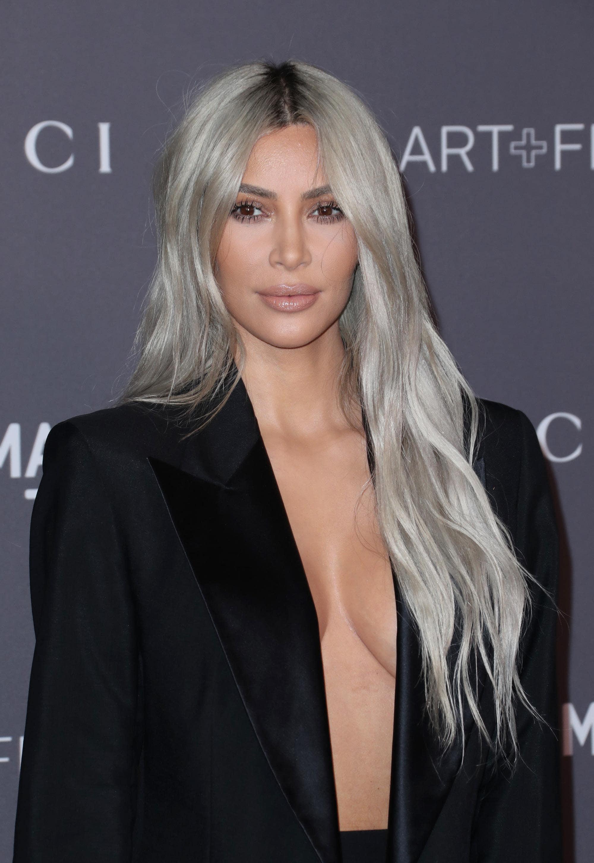 Kim Kardashian West with long wavy silver blonde hair, wearing black blazer