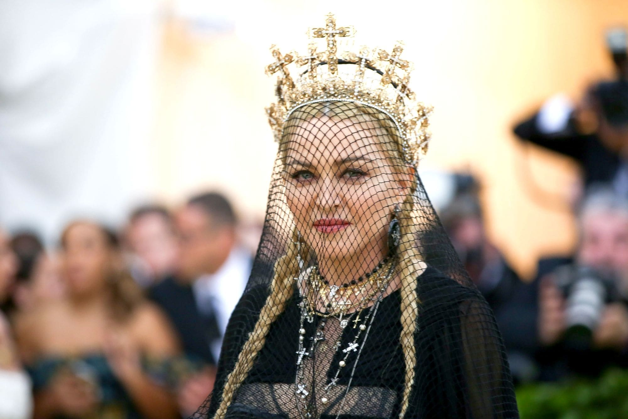Madonna at the 2018 Met Gala with her blonde hair in two pigtail braids with a black veil and gold crown.