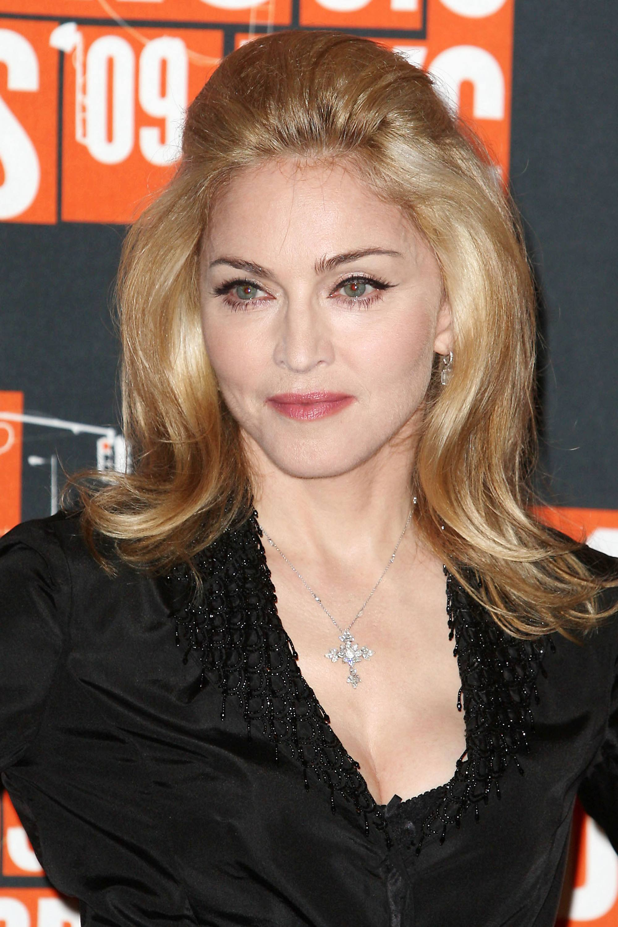 Madonna in 2009 with her honey blonde hair in a retro looking bouffant style wearing a black detailed dress