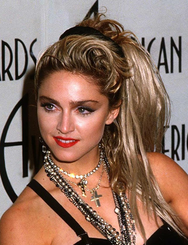 Madonna in the '80s with a messy blonde high side ponytail with a black scrunchie.