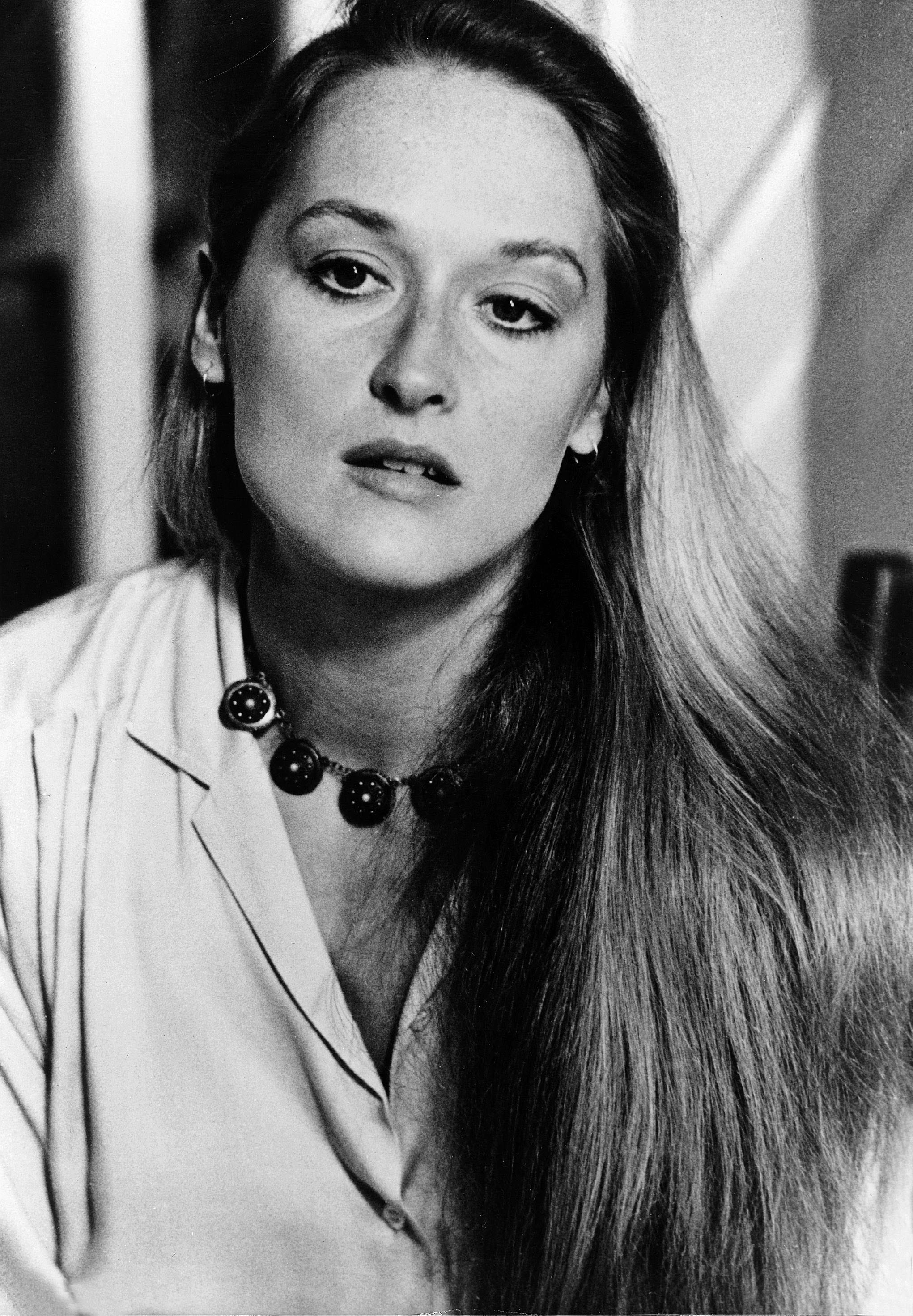 70s hairstyles: Meryl Streep long blonde straight hair swept over her shoulder in black and white image