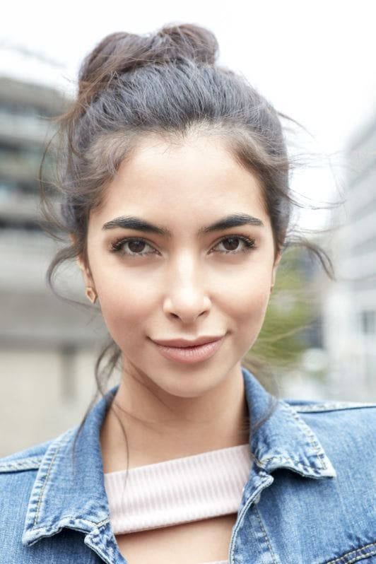 Messy bun tutorial: Close-up outdoor shot of a brunette model with her hair in a messy bun, wearing a denim jacket and lilac top