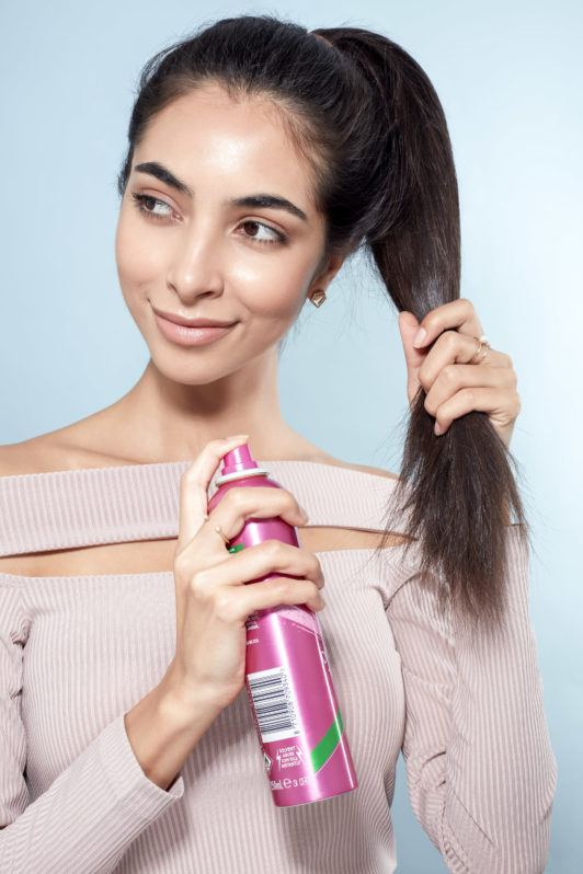 Messy bun tutorial: Close-up of a brunette model with a high ponytail spraying her hair with texturising spray, wearing a lilac top and standing against a blue background