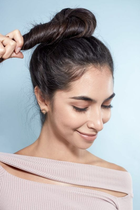 Messy bun tutorial: Close-up of a brunette model wrapping her hair into a high bun, wearing a lilac top and standing against a blue background