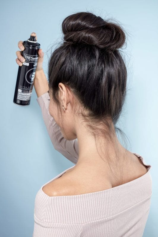 Messy bun tutorial: Back view of a brunette model with her hair in a high messy bun, spraying her hair with Tresemme hairspray, wearing a lilac off the shoulder top and standing in front of a blue background