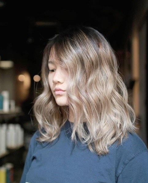 Ash blonde ombre: Photo of a woman with shoulder length wavy ash brown ombre hair