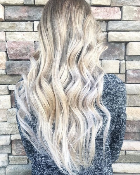 Ash blonde ombre: Back view of a woman with long wavy platinum ash blonde hair, wearing grey