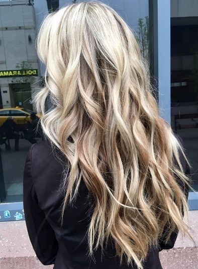 back view of a woman with waist length reverse blonde ombre hair