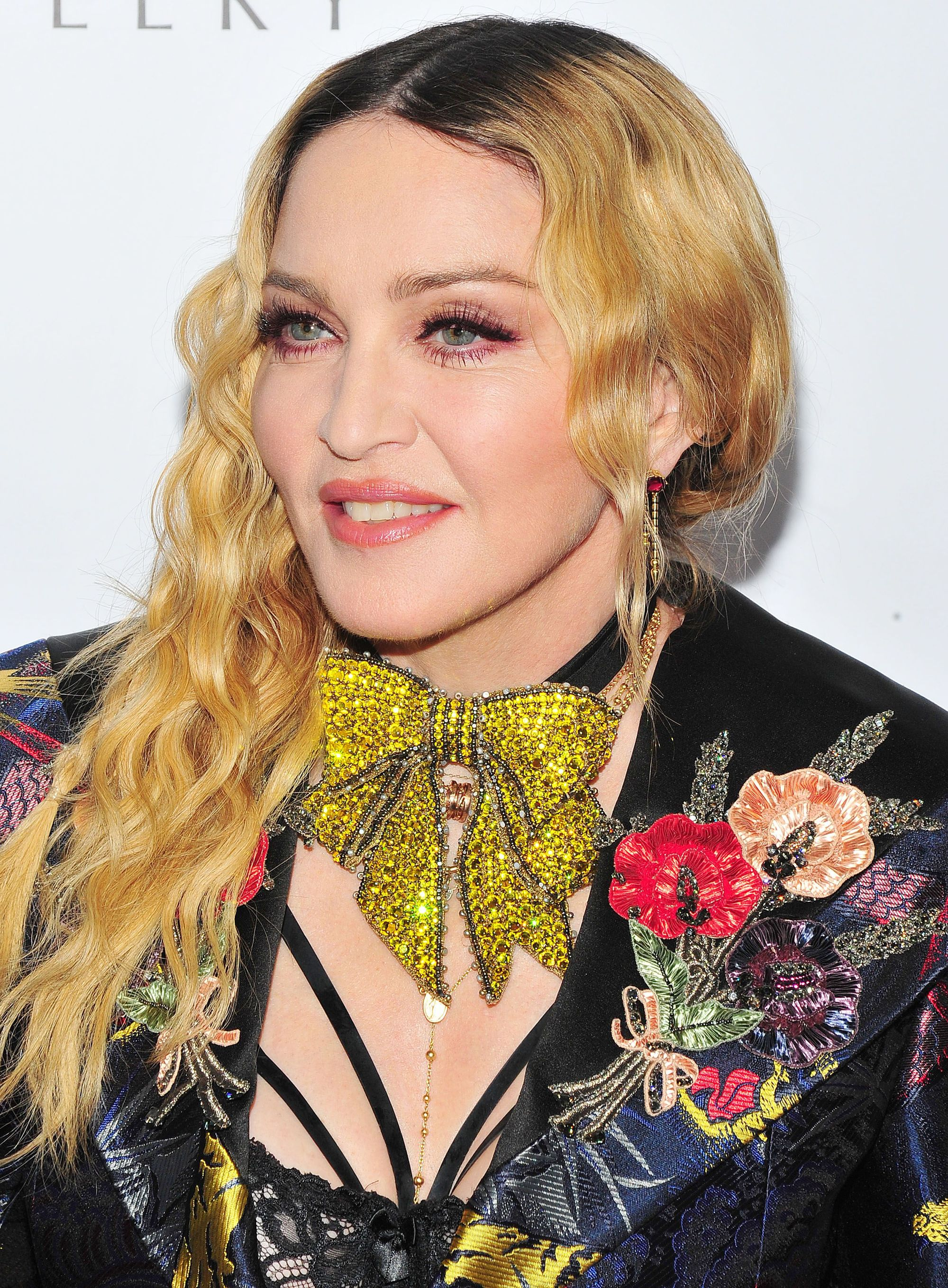 Madonna on the red carpet in 2016 with long blonde wavy hair swept over one shoulder.