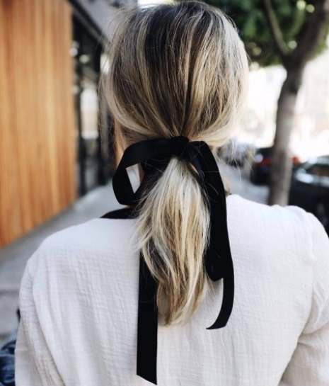 backshot of woman with low ponytail with a black ribbon hairstyle
