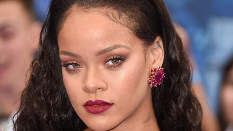Rihanna with slicked back strands wearing red on the Valerian red carpet