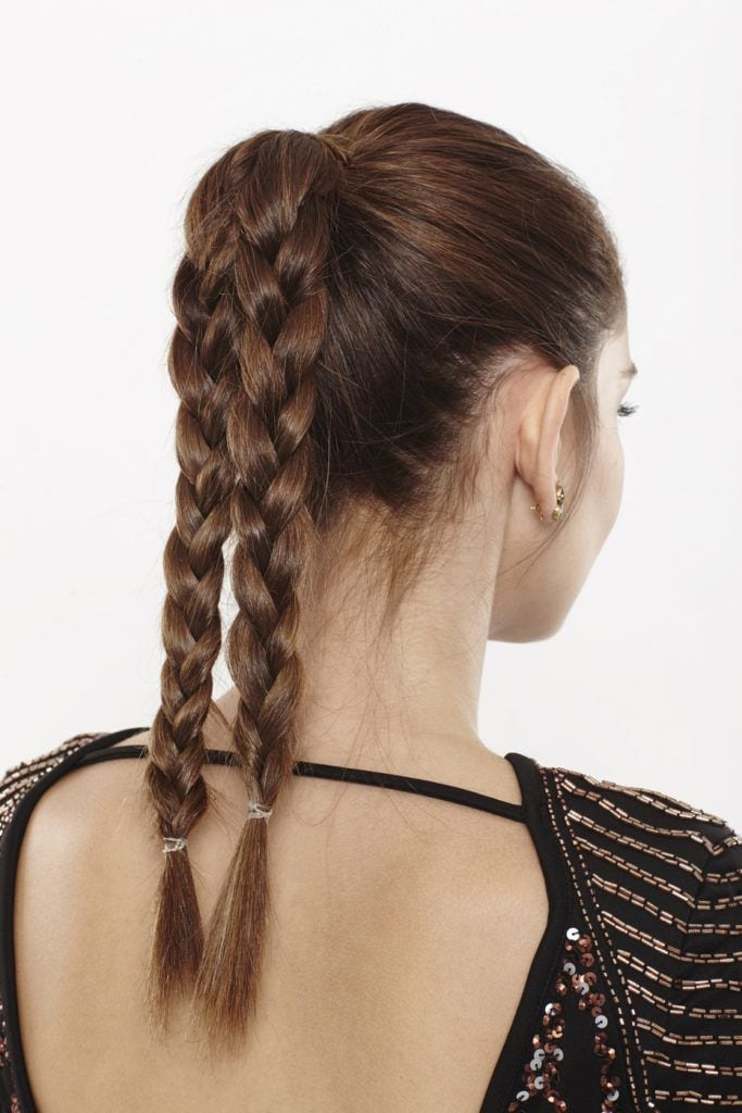 back view of a woman with two braided ponytails in brunette hair