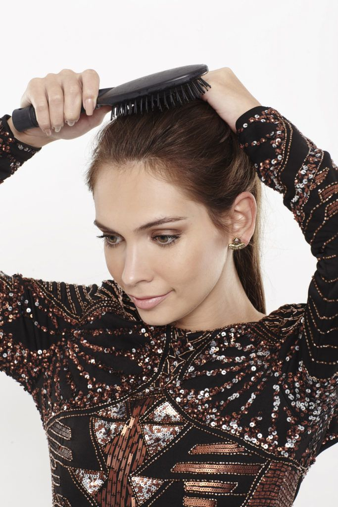 woman with brunette hair brushing her hair back into a ponytail