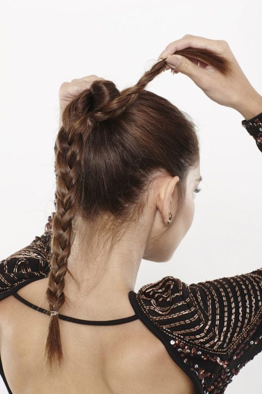 woman with brunette hair wrapping a braided ponytail into a bun
