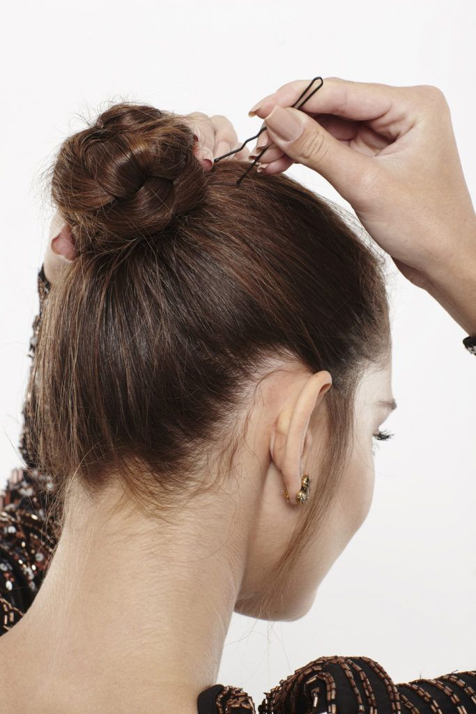 woman with brunette hair pinning her braided bun in place