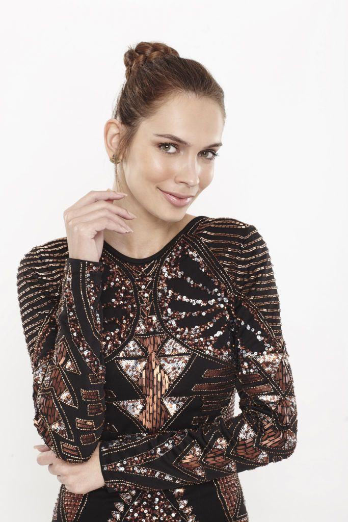 woman with brunette hair in a braided bun wearing a sparkly black dress