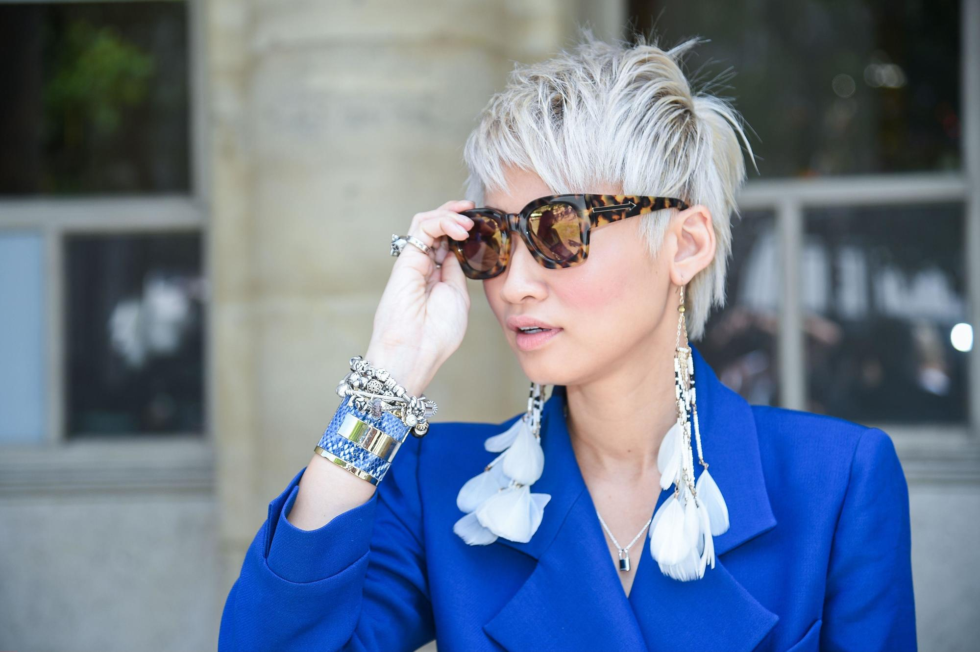 Purple conditioner for blonde hair: Street style model with short hair and a long fringe hairstyle, wearing sunglasses and blue jacket