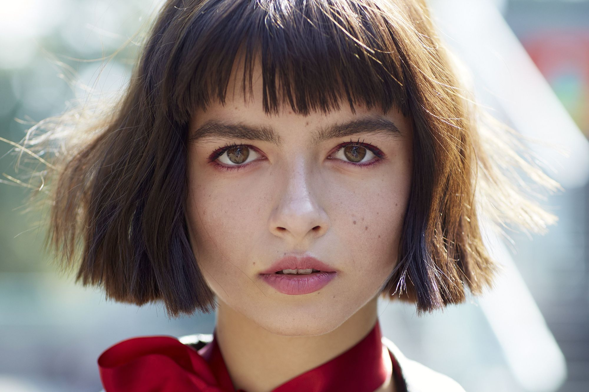 close up of street style model with short hair with fringe, wearing red scarf