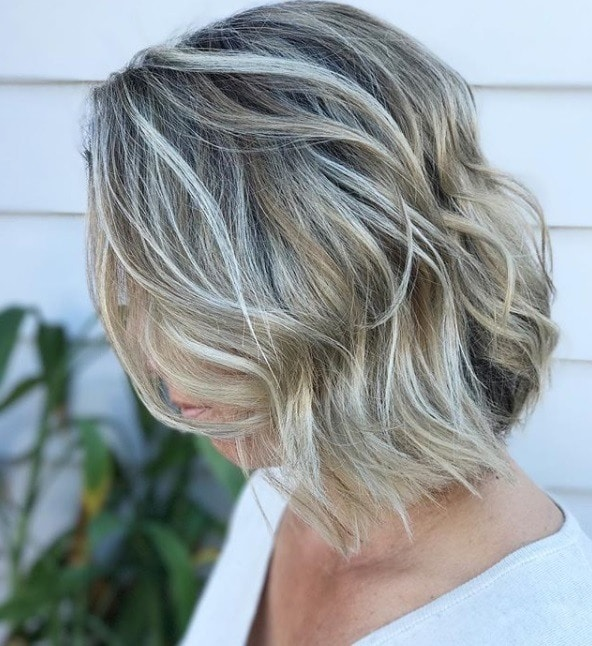 woman with wavy short blonde bob with silver highlights running through it outside