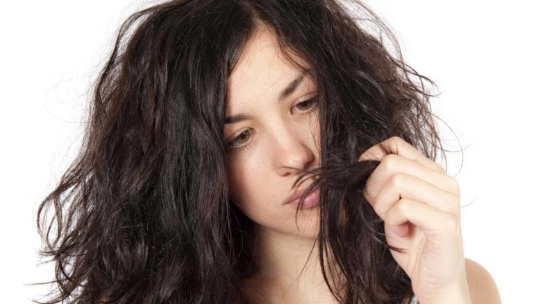 model looking at her brown frizzy hair