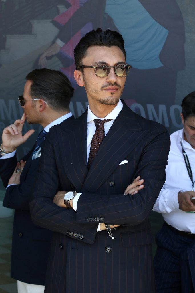 easy hairstyles for guys: street style man with swept back pomp wearing suits