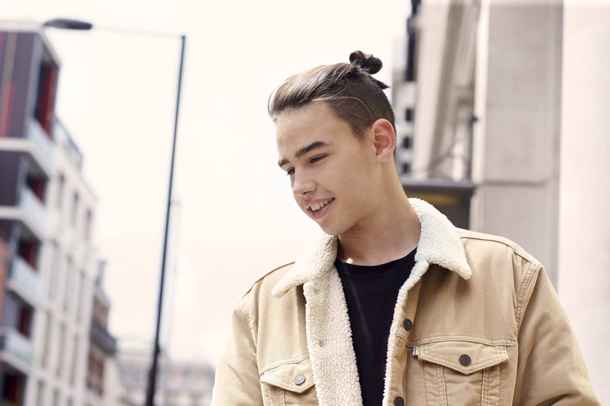 male model with black hair with man bun and high undercut fade