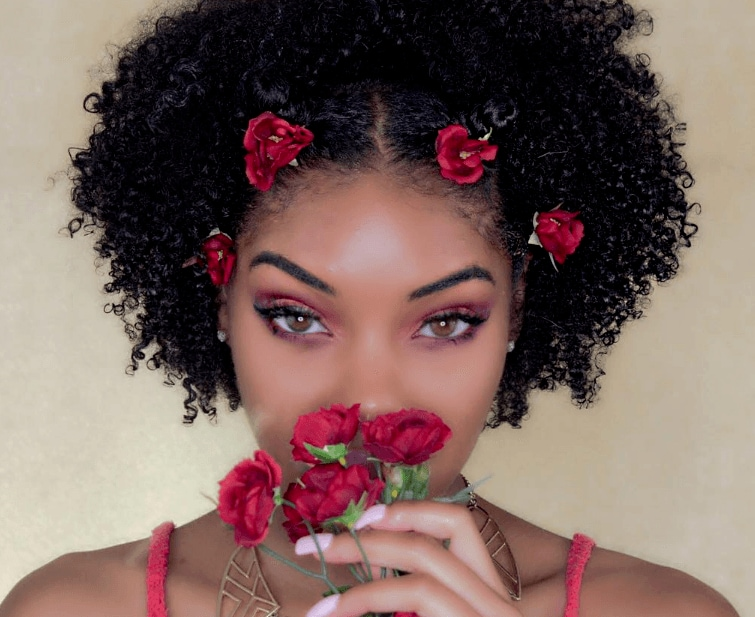 close up shot of woman with bantu knot with flowers in them