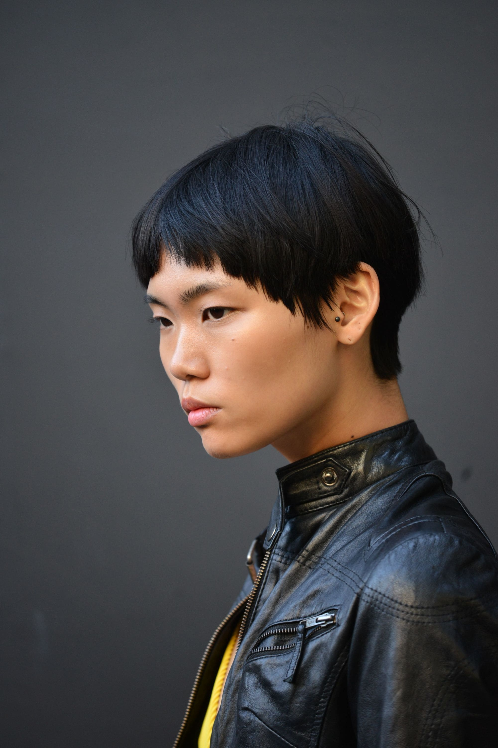 short asian hairstyles: street style shot of model with modern bowl haircut, wearing black leather jacket