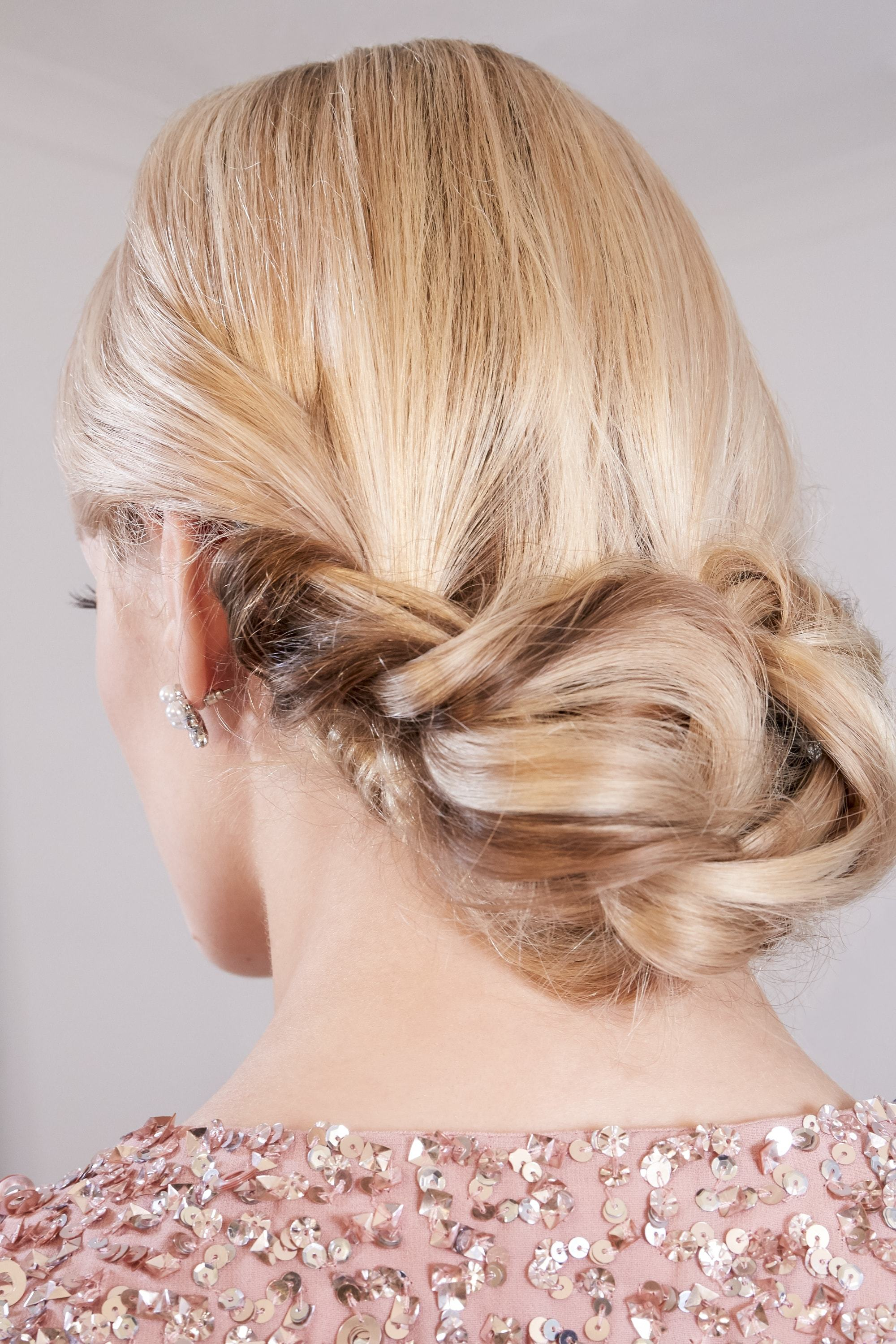 Easy braids for long hair: Back view of a blonde woman with a low twisted chignon, wearing a pink sequin dress