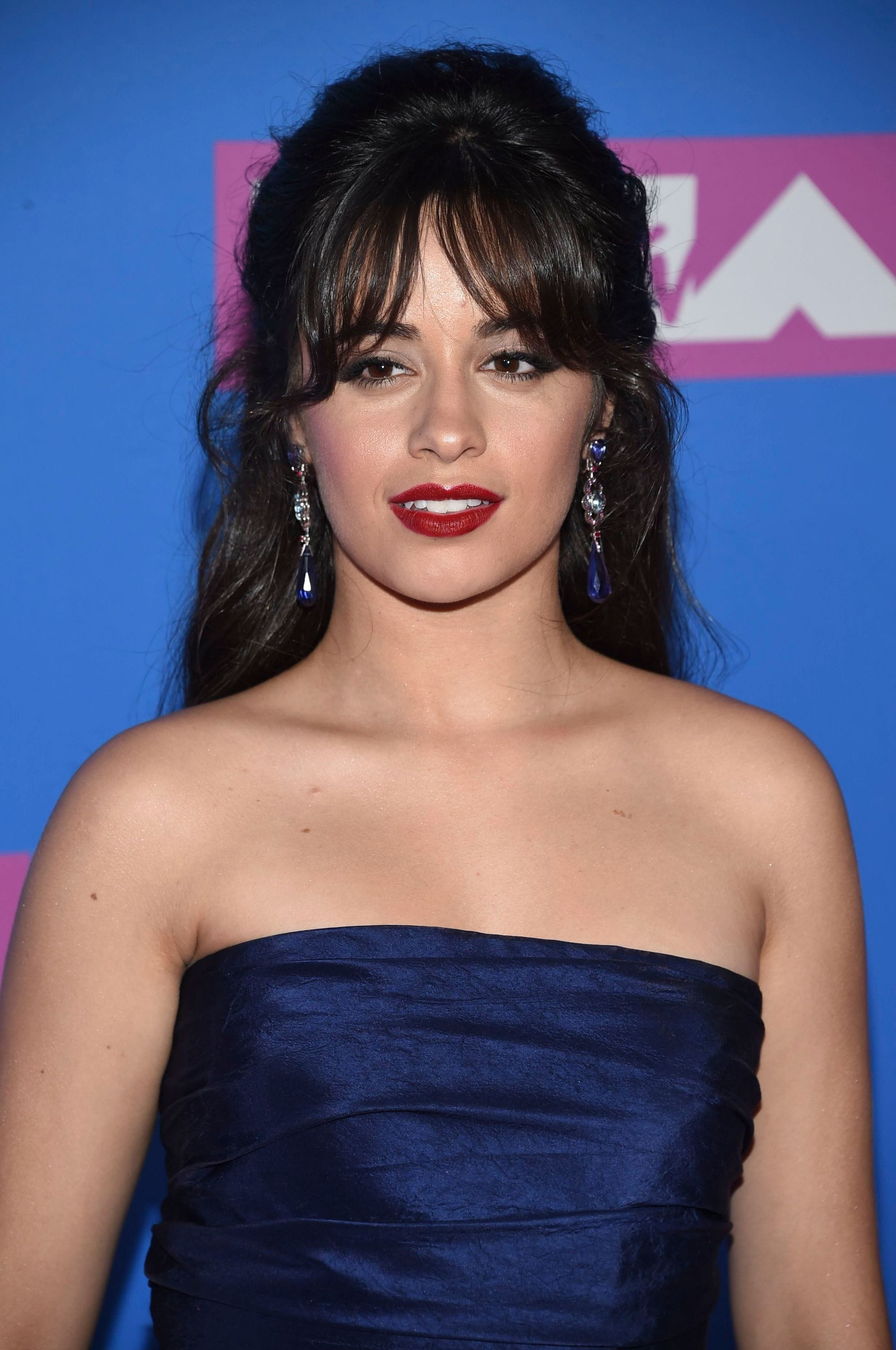 Red carpet hairstyles: Camila Cabello with long chocolate brown hair styled into a half-up, half-down updo, complete with curtain bangs on the VMA red carpet.