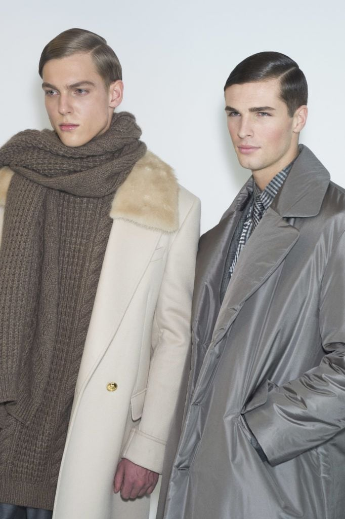 shot of male models with a classic side slick hair style on the runway wearing smart clothing