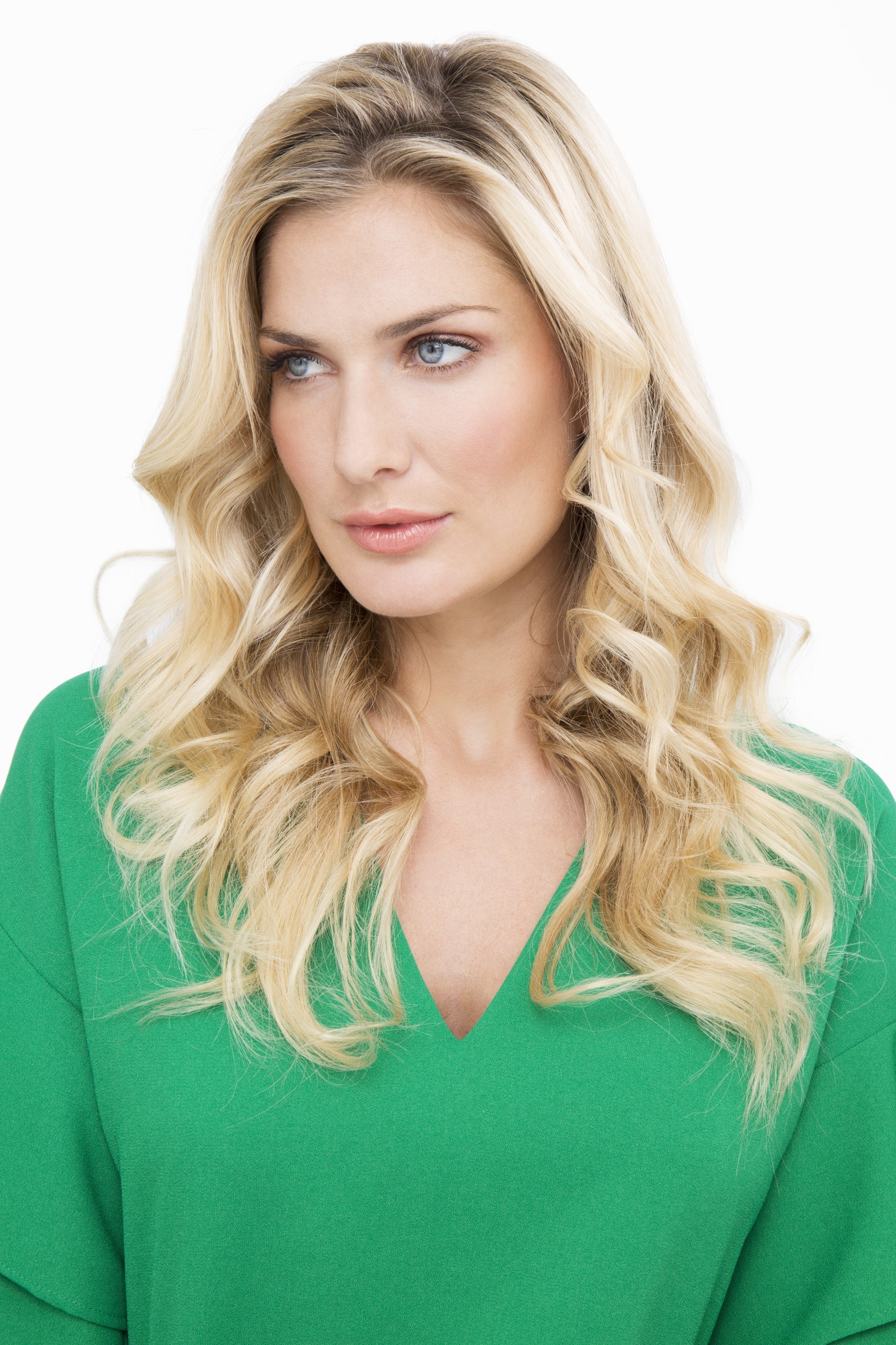 blonde model wearing a green v neck top with long curly hair