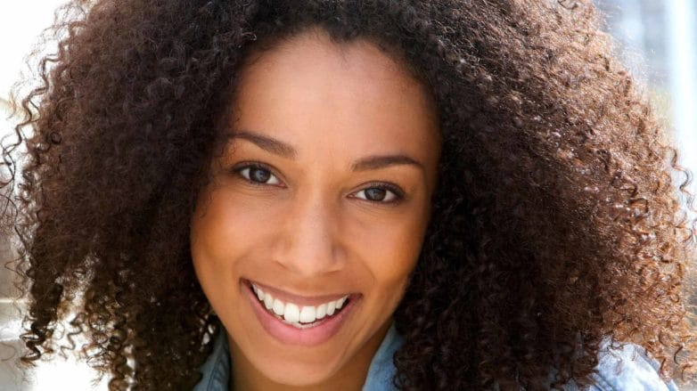 model with curly natural hair leaning against a wall