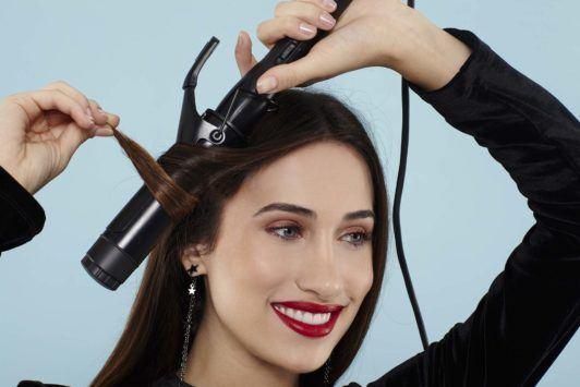 Curly ponytail tutorial: Brunette model curling her hair
