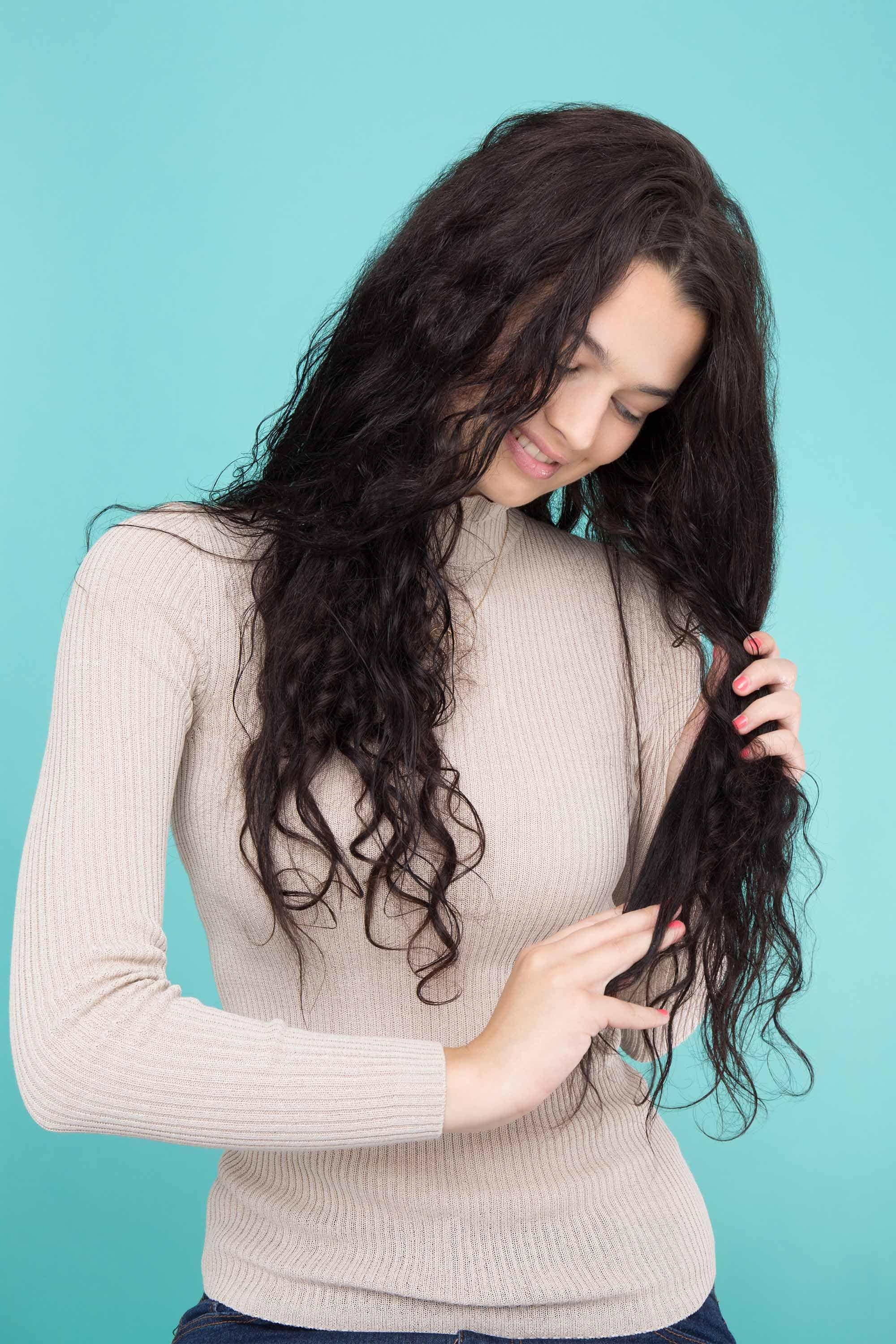 model with long dark brown curly hair looking at ends of hair