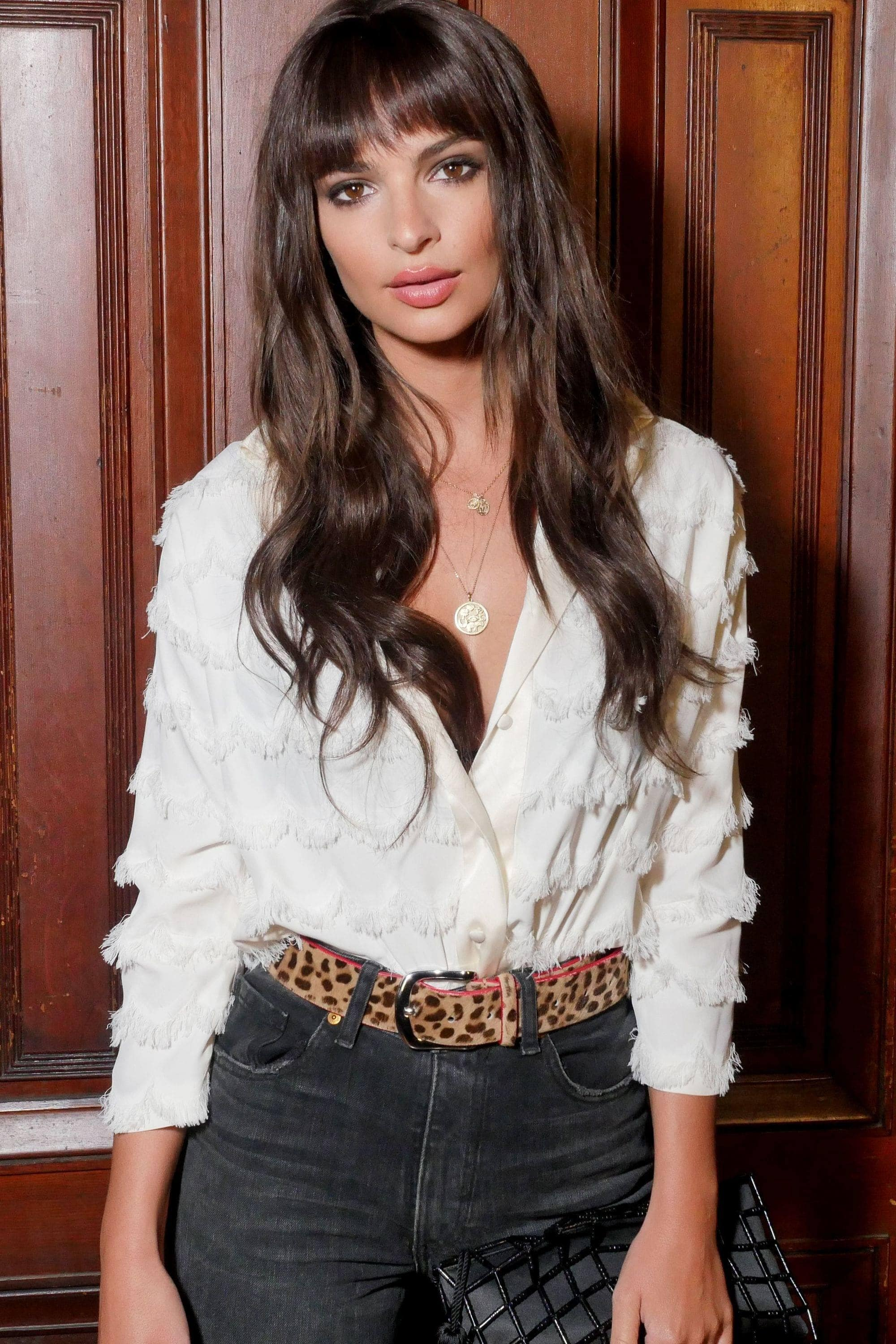 close up shot of emily ratajkowski with long brown hair with feather bangs, wearing blouse and jeans