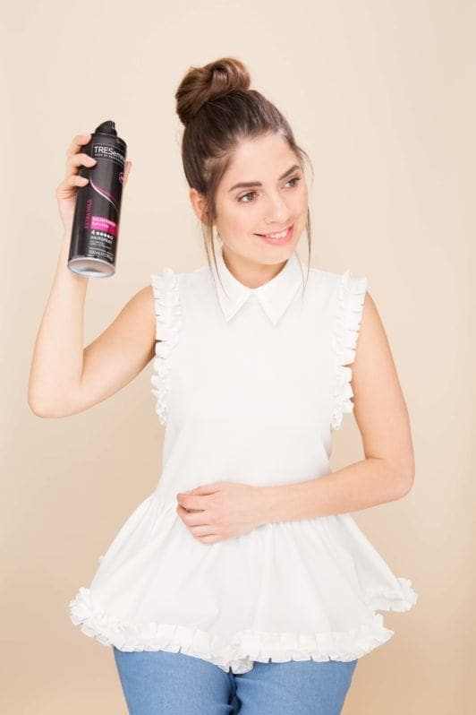 Woman with brunette hair in a topknot spraying hairspray